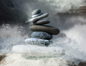Zen stones being knocked over by black ocean waves