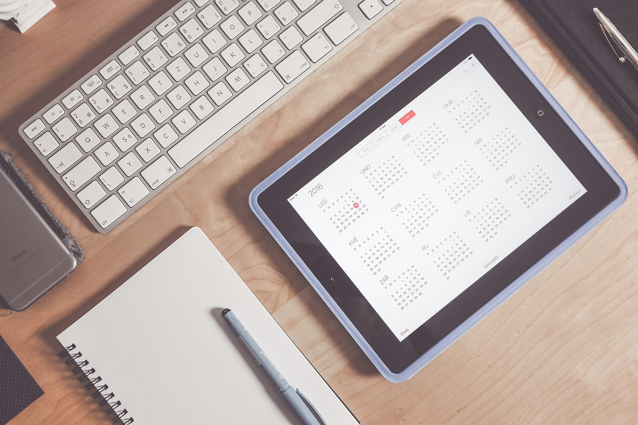 desktop with an iPad showing a calendar view, notepad and pen next to iPad with an Apple keyboard above both the iPad and the notepad