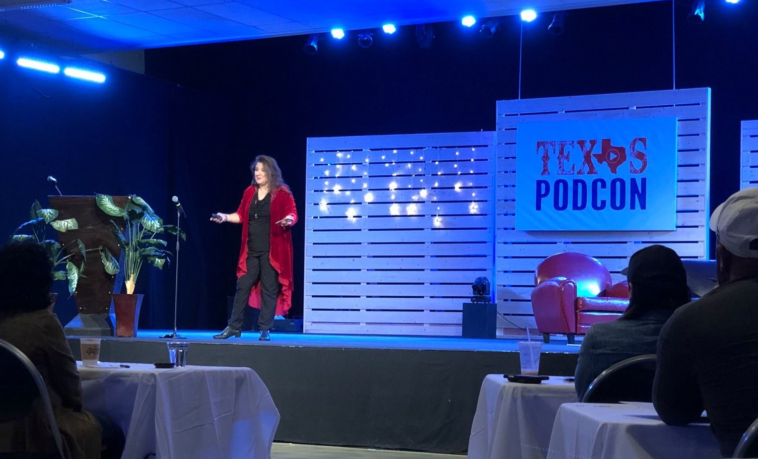 Jennifer Navarrete speaking on stage at Texas Podcast Conference in 2019