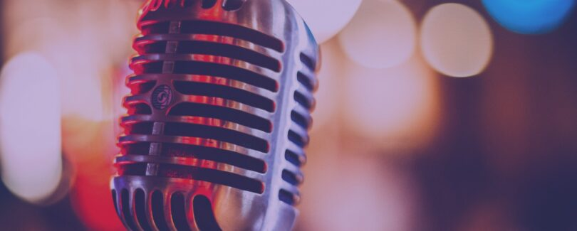 Old fashioned silver microphone in front of a mix of blurred out lights in the background