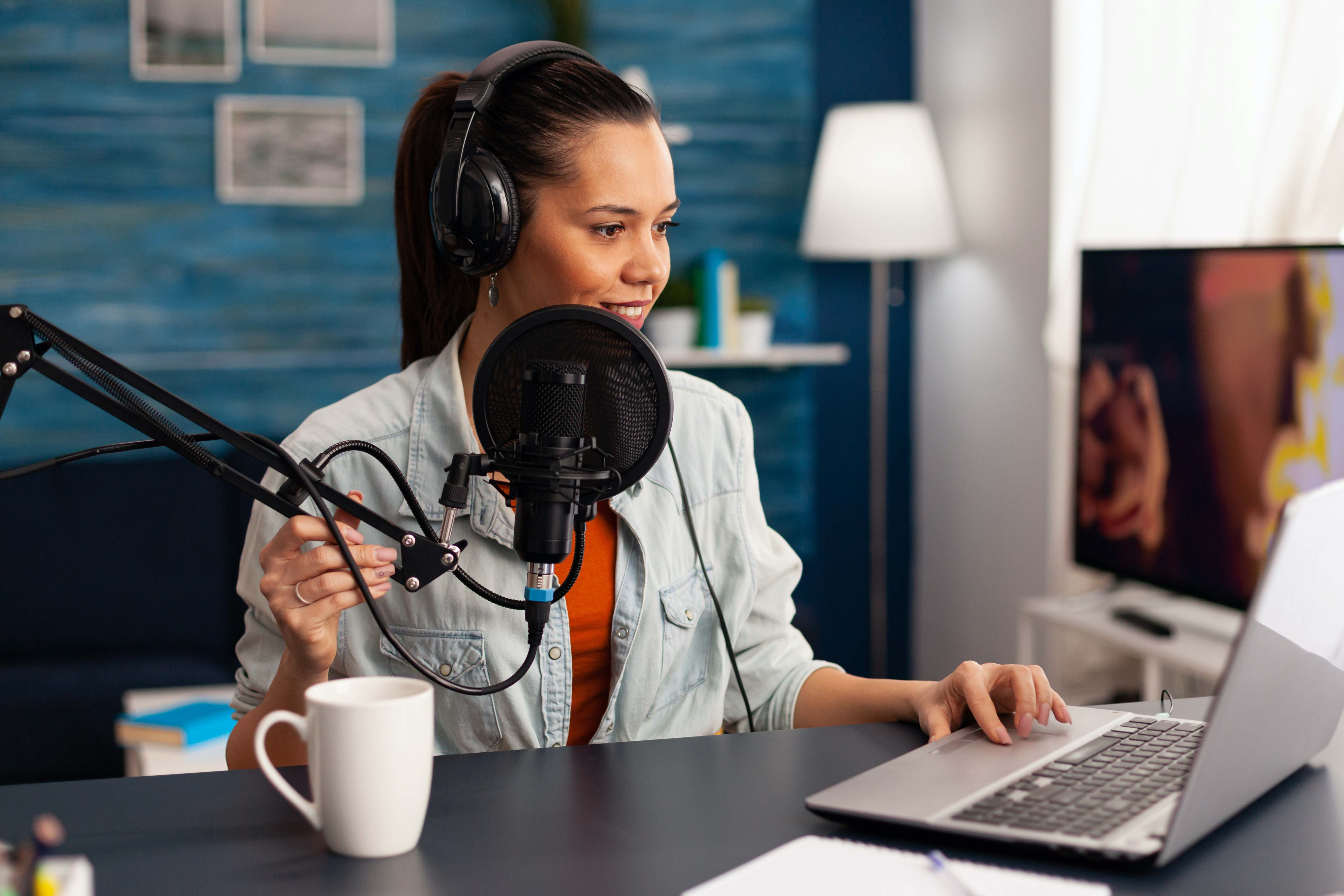Woman podcasting with mic, headphones, computer and a cup of coffee at a desk